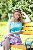 美丽的十几岁的女孩坐长凳 图库摄影