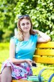 美丽的十几岁的女孩坐长凳 免版税库存照片