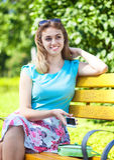 美丽的十几岁的女孩坐长凳 库存照片