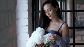 美丽的半穿戴的浅黑肤色的男人支持与一花束的窗口在她的手上 影视素材