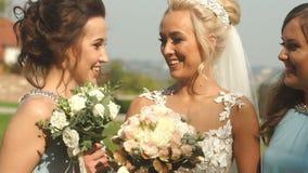 美丽的华美的新娘的画象有可爱的微笑的笑并且获得与她迷人的女傧相的乐趣 影视素材