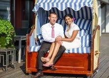 美丽的印地安新娘和白种人新郎,海滩睡椅的。 免版税库存图片