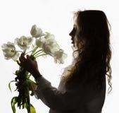 美丽的卷曲女孩剪影有春天的开花在白色背景的郁金香 免版税库存图片