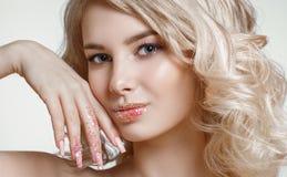 美丽的卷曲blondy妇女特写镜头画象有完善的艺术构成的,与闪烁的时髦结霜的钉子设计 库存照片