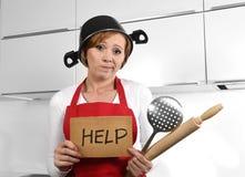美丽的厨师妇女被迷惑和佩带红色围裙的被挫败的面孔表示请求拿着滚针的帮忙 免版税图库摄影