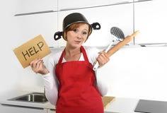 美丽的厨师妇女被迷惑和佩带红色围裙的被挫败的面孔表示请求拿着滚针的帮忙 免版税库存图片
