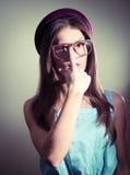 美丽的反对轻的墙壁背景的女孩佩带的玻璃的图片 库存图片