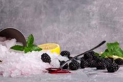 美丽的发光的白色冰块 冰用成熟黑莓、酸柠檬、点心用匙和莓果糖浆在灰色 免版税库存照片