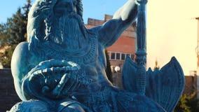 美丽的古铜或海王星石雕象在拿着在左手的一个在人一个的冠的三叉戟和贝壳反对 股票录像