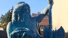 美丽的古铜或海王星石雕象在拿着在左手的一个在人一个的冠的三叉戟和贝壳反对 影视素材