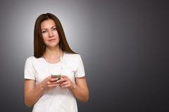 美丽的可爱的偶然少妇联系在她的移动电话 工作室被射击在灰色背景 免版税库存图片