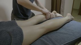 美丽的可爱的妇女在得到她的腿的温泉中心由一位悦目男性治疗师按摩了反脂肪团- 股票视频