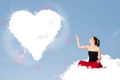 美丽的可爱的妇女坐与心脏的云彩 免版税库存图片