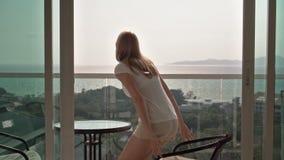美丽的可爱的妇女对阳台打开滑门 去外面并且坐椅子放松 股票录像