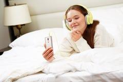 美丽的可爱的年轻欧洲妇女深色的早晨在与看在智能手机面孔的电话的白色床上微笑作l 库存照片