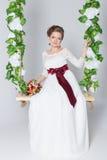 美丽的可爱的新娘坐与五颜六色的花美丽的花束的摇摆在一件白色礼服的有晚上发型的 免版税库存图片