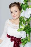 美丽的可爱的新娘坐与五颜六色的花美丽的花束的摇摆在一件白色礼服的有晚上发型的 免版税图库摄影