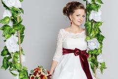 美丽的可爱的新娘坐与五颜六色的花美丽的花束的摇摆在一件白色礼服的有晚上发型的 免版税库存照片