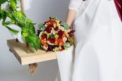美丽的可爱的新娘坐与五颜六色的花美丽的花束的摇摆在一件白色礼服的有晚上发型的 库存图片
