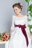 美丽的可爱的新娘坐与五颜六色的花美丽的花束的摇摆在一件白色礼服的有晚上发型的 图库摄影