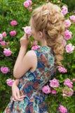 美丽的可爱的柔和的性感的女孩近开花的玫瑰丛在夏天温暖与美丽的头发的天 库存图片