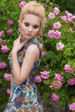 美丽的可爱的柔和的性感的女孩近开花的玫瑰丛在夏天温暖与美丽的头发的天 免版税库存图片