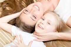美丽的可爱的母亲或姐妹有儿童女孩说谎的面对面的愉快的微笑的&看的照相机的 免版税库存照片