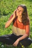 美丽的可爱的深色的女孩在手机坐草甸并且谈话 免版税图库摄影