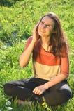 美丽的可爱的深色的女孩在手机坐草甸并且谈话 免版税库存照片
