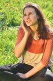 美丽的可爱的深色的女孩在手机坐草甸并且谈话 库存图片