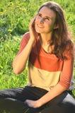 美丽的可爱的深色的女孩在手机坐草甸并且谈话 库存照片