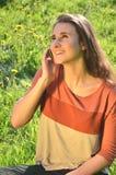 美丽的可爱的深色的女孩在手机坐草甸并且谈话 图库摄影