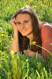 美丽的可爱的深色的女孩在草甸说谎 免版税库存图片
