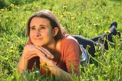 美丽的可爱的深色的女孩在草甸说谎 免版税库存照片