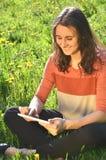 美丽的可爱的深色的女孩坐有片剂的一个草甸 免版税图库摄影