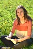 美丽的可爱的深色的女孩坐有片剂的一个草甸 免版税库存图片