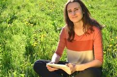 美丽的可爱的深色的女孩坐有片剂的一个草甸 库存照片