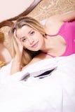 美丽的可爱的迷人的甜年轻白肤金发的妇女特写镜头画象绯红色衬衣的有片剂在床上的个人计算机计算机的 图库摄影