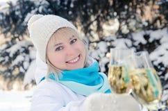 美丽的可爱的金发碧眼的女人在她的手上使一杯香槟叮当响庆祝新年 免版税库存图片