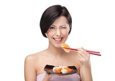 美丽的吃的寿司妇女 免版税库存照片