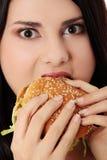 美丽的吃的汉堡包妇女 免版税图库摄影