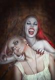 美丽的吸血鬼妇女和她的受害者 库存照片