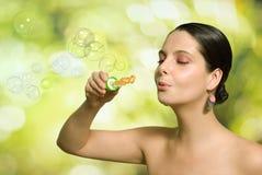 美丽的吹的泡影妇女 免版税库存照片