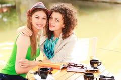 美丽的咖啡饮用的微笑二名妇女 免版税库存照片