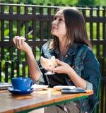 美丽的咖啡馆奶油色吃的愉快的冰妇女 库存图片