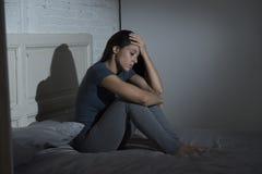 美丽的哀伤和沮丧的拉丁妇女坐床在家挫败了遭受的消沉 免版税库存照片