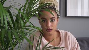 美丽的哀伤的年轻女人调查照相机在室内植物附近 股票录像