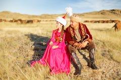 美丽的哈萨克人妇女和人全国服装的 图库摄影