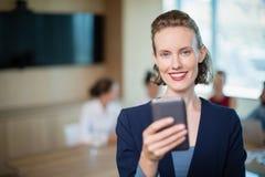 美丽的商业主管谈话在她的手机在会议室 库存照片