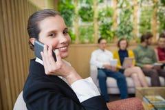 美丽的商业主管谈话在她的手机,当坐在办公室大厅时 库存照片